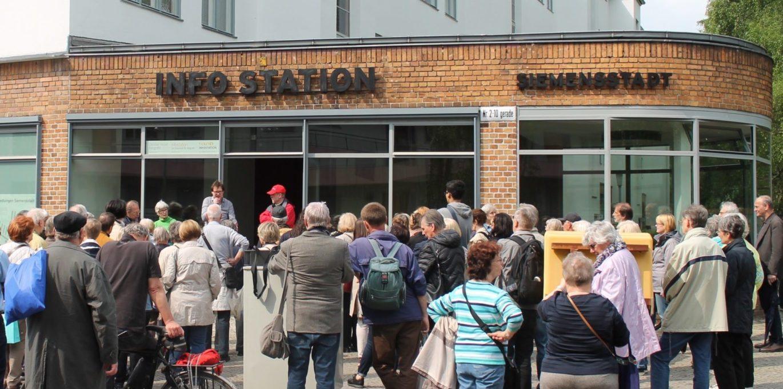 Menschenmenge vor der Infostation Siemensstadt. Der 185. Kiezspaziergang mit Bezirksbürgermeister Naumann.