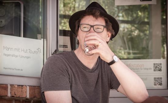 """Christian Fessel von """"Mann mit Hut Touren"""" trinkt ein Glas Wasser"""